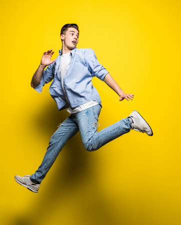 handsome man casual dressed celebrating and jumping on yellow
