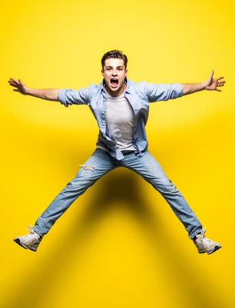 Young handsome man jumping on yellow background.