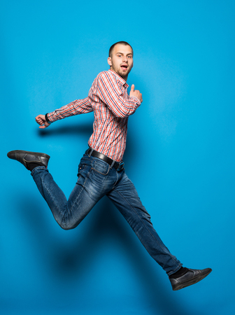 young casual man jumping for joy on blue