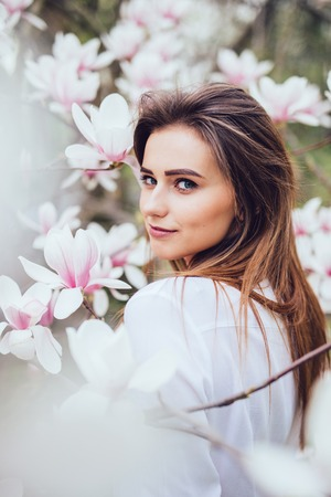 Portrait of sweet lovely girl in Magnolia blossoming flowers