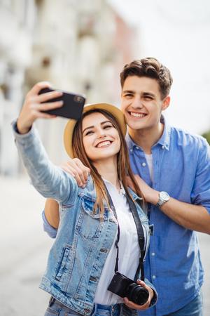 Happy tourists taking selfie on city street