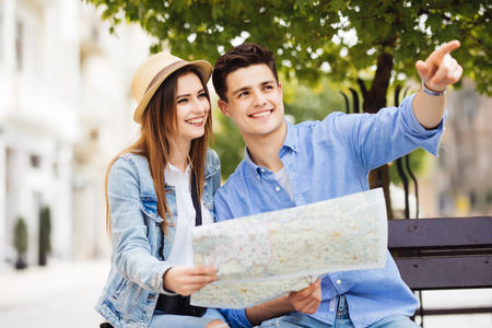 Happy tourists sightseeing city with map traveling
