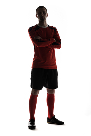 Silhouette of young football player isolated on white