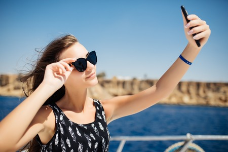 Young beautiful brunette girl making selfie using phone while sitting on the luxury yacht Banque d'images - 100179887
