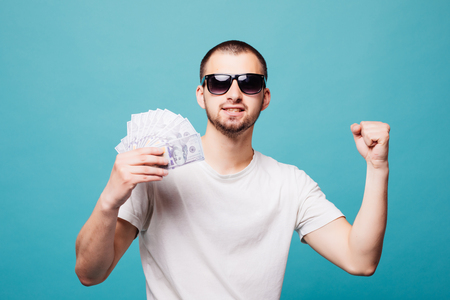 Portrait of a young summer man on white t-shirt holding cash money while smiling on you isolated on green background