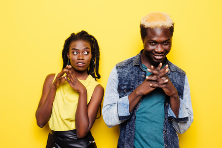 Portrait of a surprised young african couple dressed in summer clothes celebrating isolated over yellow background