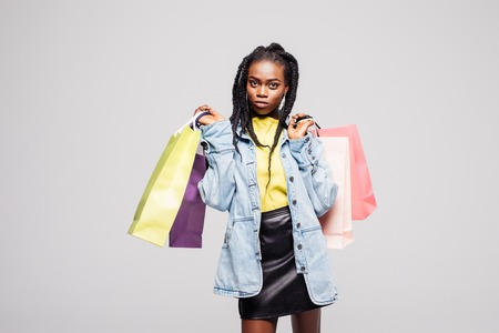 Young beauty afro american woman holding color shopping bags isolated on gray Banque d'images