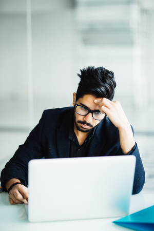 Photo of an Indian male frustrated with work sitting in front of a laptop.