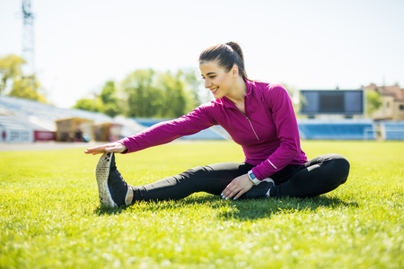 Young sport woman stretches her leg on stadium green grass, healthy lifestyle concept