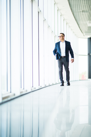 Senior businessman walking in modern office building. Successful business man wearing suit and tie.