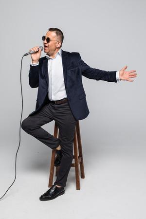 Portrait of senior man singing karaoke in white