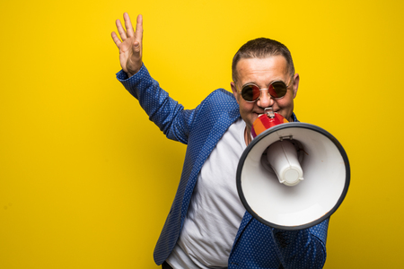 Mature businessman in sunglasses speaking with loudspeaker isolated on yellow background