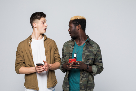 Two multiracial friends use their mobile phone isolated on white background