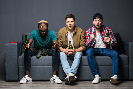 group of exited men sitting together on couch, watching television holding beers.