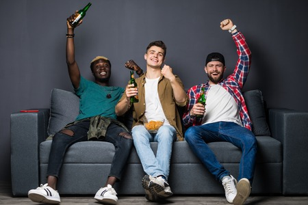 friendship, sports and entertainment concept happy male friends watching sports on tv