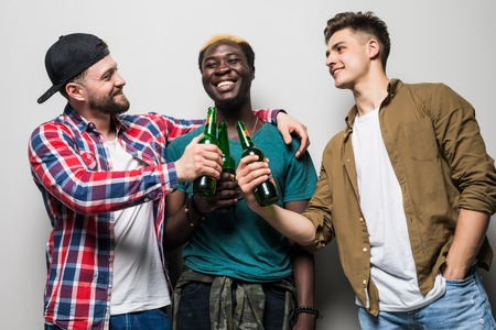 Three young joyful men holding beer and celebrating over gray background