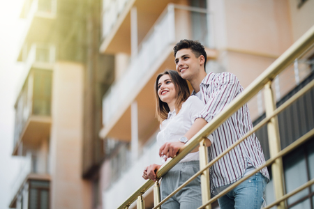 romantisches glückliches Paar entspannen und Spaß auf dem Balkon in ihrer neuen Wohnung haben
