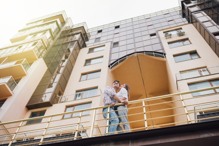 Young couple on front of new big modern house their new home