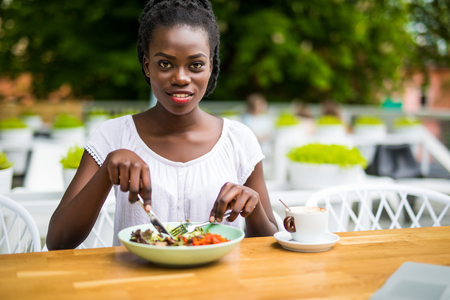 Young afro american woman sitting in street cafe outdoors eat fresh salad