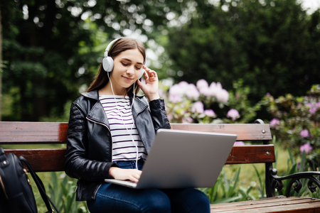 Student sitting on bench listening to music and using laptop and wearing headphones