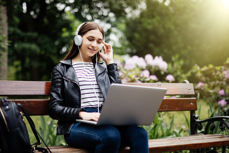 Smiling student sitting on bench listening music and holding laptop in park at school Standard-Bild