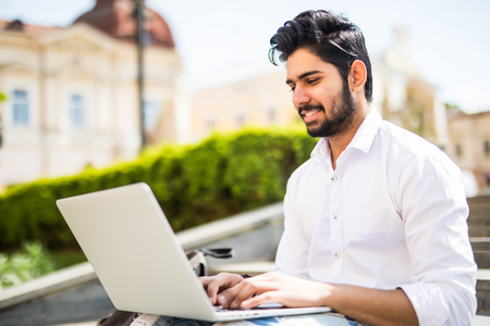 East Indian American College Student sits on stairs on campus, works on laptop computer.