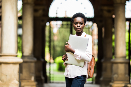 Young beautiful black woman holding laptop at campus background. University, technology, business concept