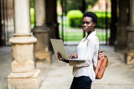 Portrait of smiling African american student doing homework outdoors using laptop for research .Positive dark skinned hipster girl styling in university campus preparing for examinations outdoors
