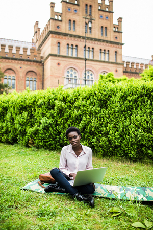 African american international student typing on laptop preparing for examination outdoors in campus enjoying weather. Smiling female copywriter work on publication for network sitting on grass