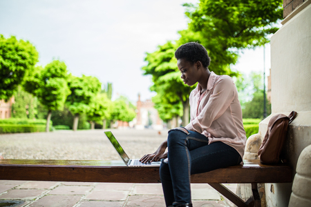 Young afro american female IT specialist working remotely on a new project using a public network wifi while sitting on a wooden bench. Pretty student girl using laptop computer for work at campus