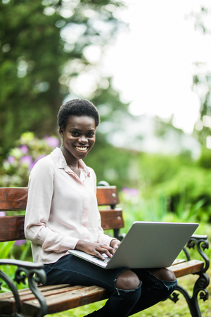 Young afro american woman sitting on wooden bench in the park and working on laptop Stock Photo