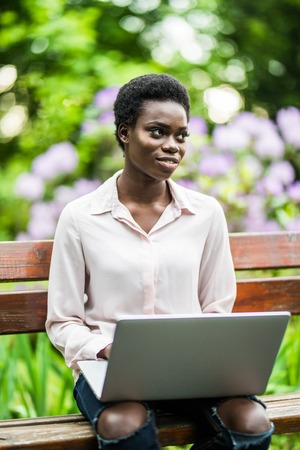 Young afro american woman sitting on wooden bench in the park and working on laptop 스톡 콘텐츠