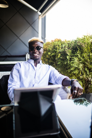 Young handsome business african young man using tablet in outdoor cafe Stock Photo