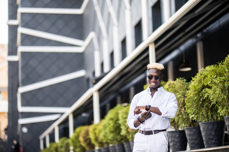 Handsome Afro American business man look at watch while waiting outdoors for someone Stock Photo