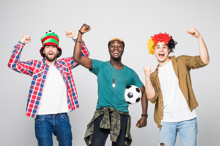 Yes. Winners. Three cheerful young men are standing and gesturing for the victory on white background in casual outfit and jeans.