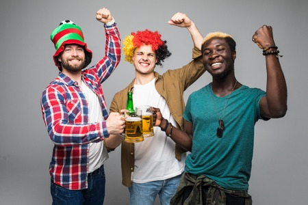 Three young cheerful men holding beer and celebrating isolated over white
