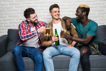 Close up portrait of attractive, stylish, cheerful men holding bottles with lager in hands, watching soccer word cup competition, cheering for favorite team 写真素材