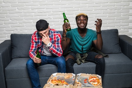 Domestic life. Two young mixed race men watching a football match on tv with different emotiond of win and lose. Sport fans
