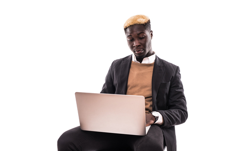 Portrait of confident afro business man dressed in classic elegant suit using netbook for work isolated on gray background