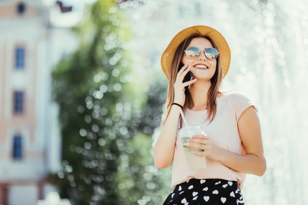 Smiling young woman teenager talking phone on summer street drinking mojito outdoor Zdjęcie Seryjne