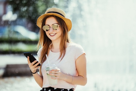 Young beautiful brunette woman with a cold drink sitting in the street typing on the phone