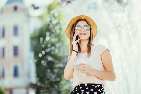 Beautiful young woman in sunglasses and hat in cafe drinking mojito refreshing cocktail while talking on the phone on sunny day