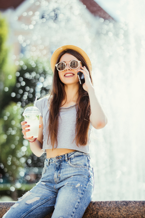 Young beautiful stylishly dressed girl is walking along the streets of the city, drinking juice, coffee, talking on mobile phone