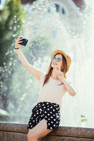 Beautiful young woman drink mojito doing selfie in the summer city street Zdjęcie Seryjne