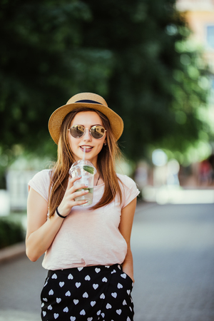 Pensive happy woman sipping a mojito in the street outdoors Stock Photo
