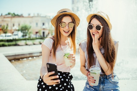Two female best friends recreat together against fountain, look cheerfully at modern smart phone, message with friends, connected to wireless internet and drink fresh cocktails