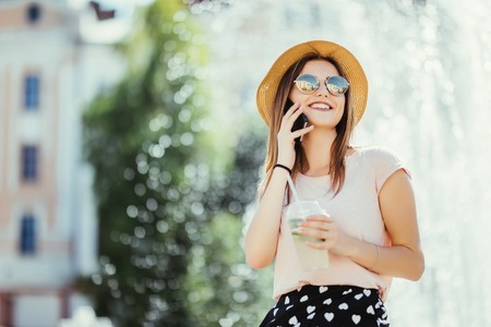 Smiling young woman teenager talking phone on summer street drinking mojito outdoor Stock Photo