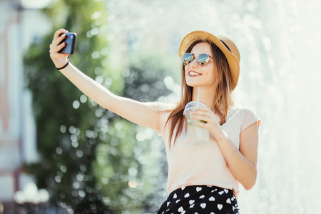Young girl take selfie from hands with phone on summer city street. Urban life concept. Stock Photo