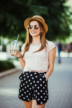 Portrait of young woman with mojito resting on city street
