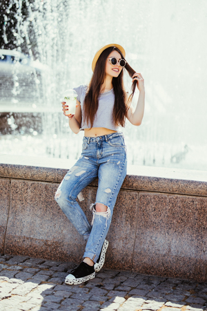 Smiling positive funny young woman holding cup drink, sunlight, outdoor, street style Stock Photo